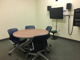 Image of room with table, chairs, and tv screen