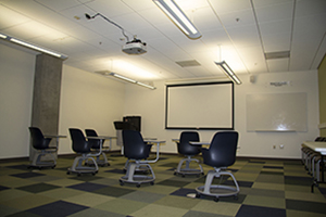 Image of room with chairs, screen, and white board