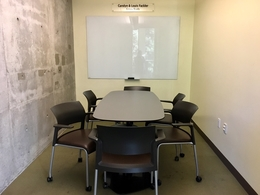 Image of room with table, chairs, and white board