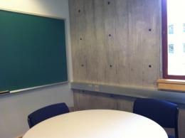 Image of room with table, chairs, and chalk board