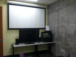 Image of room with projector screen, tv screen, and dvd/vhs player