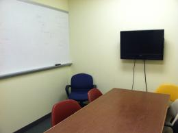 Image of room with computer monitor, table, chairs, and white board