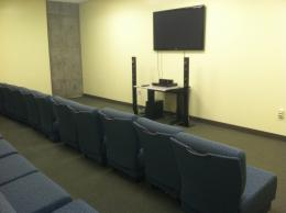Image of large room with chairs, dvd player, and large tv screen