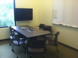 Image of room with table, chairs, tv screen, and white board